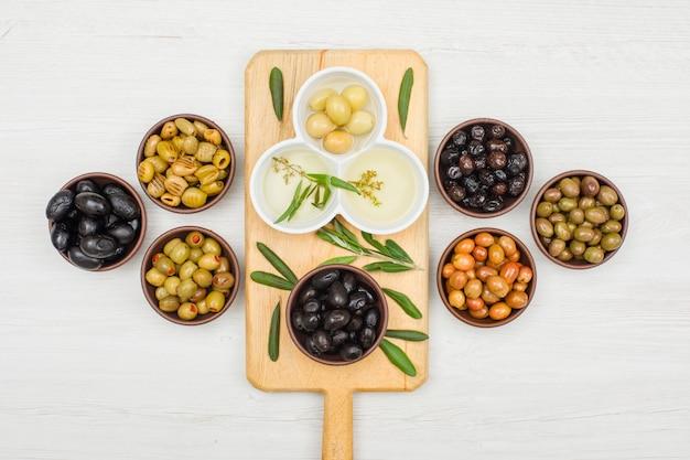 Olives Marinées Et Huile D'olive Dans Des Bols Et Une Planche à Découper Avec Des Feuilles D'olivier Vue De Dessus Sur Bois Blanc Photo gratuit