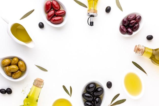 Olives noires rouges et jaunes à plat en cuillères avec bouteilles d'huile et espace de copie Photo gratuit