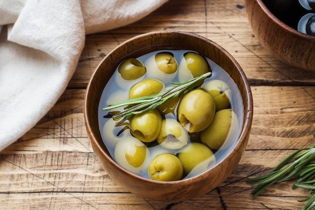 Olives Noires Et Vertes Dans Des Bols En Bois Sur Une Table En Bois Photo Premium