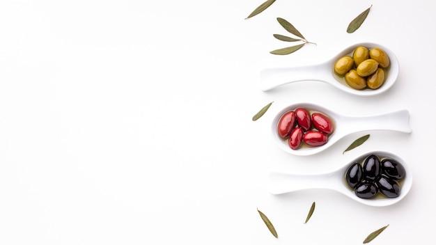 Olives rouges noires jaunes en cuillères à feuilles et espace de copie Photo gratuit
