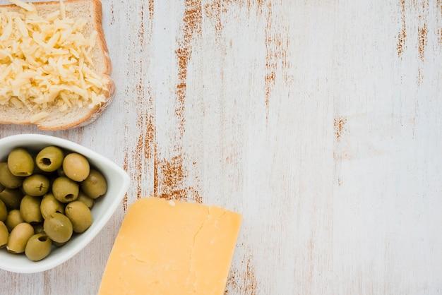 Olives vertes dans un bol blanc; fromage râpé sur du pain sur le bureau blanc Photo gratuit