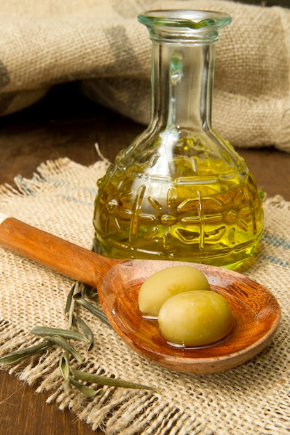 Olives vertes fraîches sur la cuillère et l'huile Photo Premium