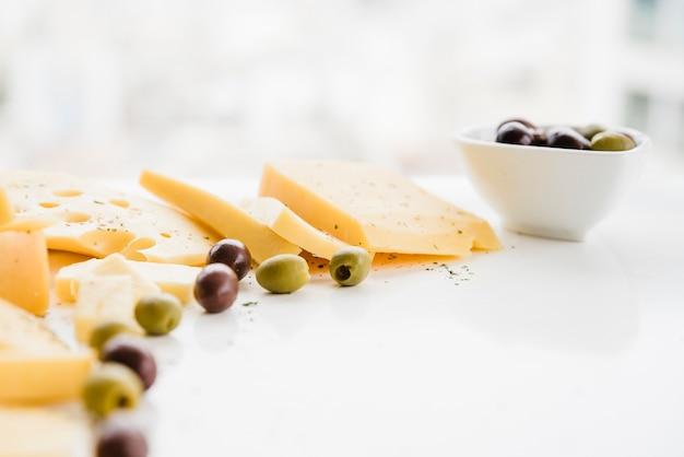 Olives vertes avec des tranches de fromage sur le bureau blanc Photo gratuit