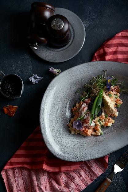 Olivier à la chair de crabe dans un beau bol au m des huîtres, sur un fond sombre. la nourriture en aucun cas, le de la mode alimentaire. alimentation saine. Photo Premium