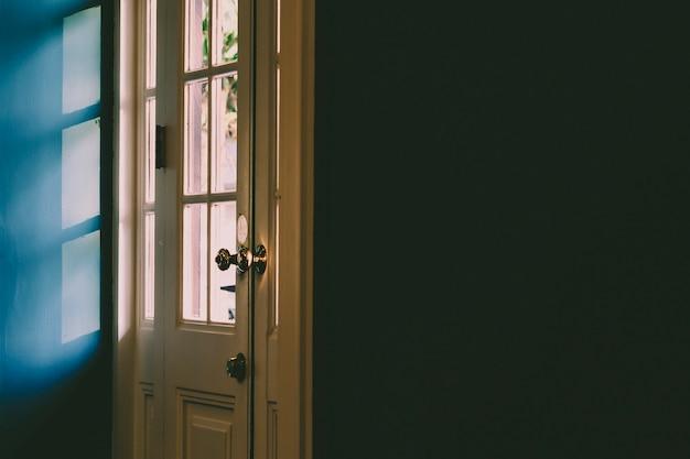 Ombre à travers la porte, mur noir Photo Premium