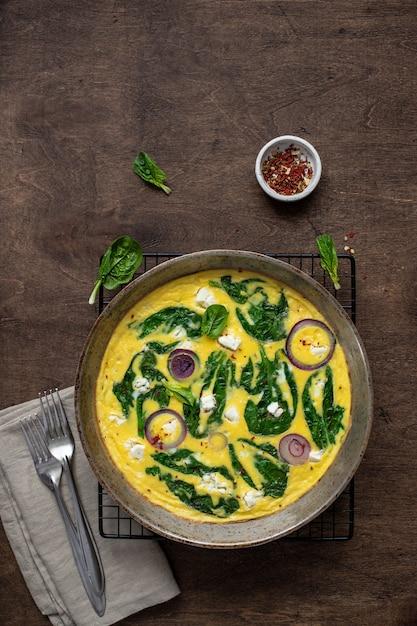 Une omelette ou une frittata faite maison avec des épinards, du fromage feta et des oignons rouges dans une poêle en fer sur une table rustique. vue de dessus Photo Premium