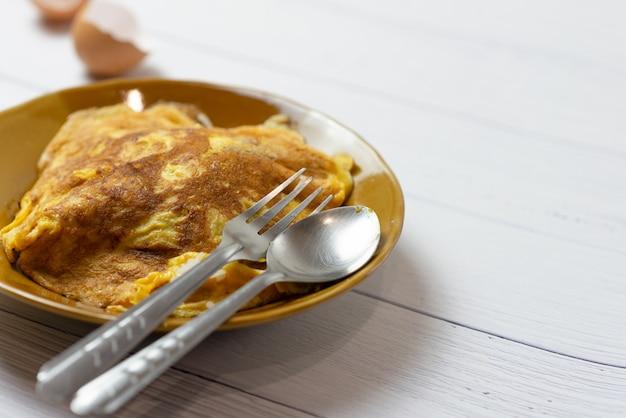 Omelette Thaïlandaise Ou œuf Au Plat, Petit Roussi Sur Un Plat En Céramique Brun Avec Une Cuillère. Photo Premium