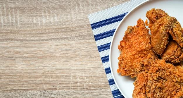 Op vue plat de poulet frit au fond de table en bois de restaurant Photo Premium