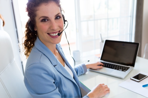 Opérateur de service client parlant au téléphone dans le bureau. Photo gratuit