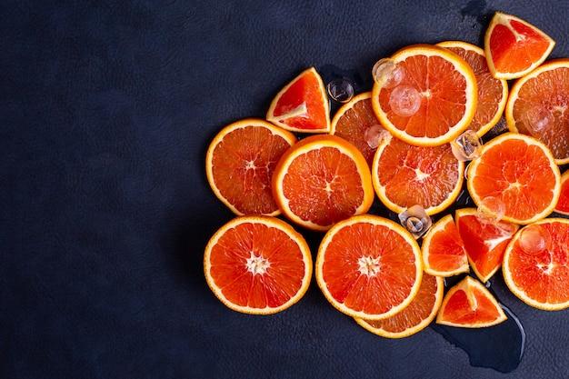 Orange Rouge Frais Ou Pamplemousse Avec De La Glace Sur Un Fond Classique Bleu. Agrumes Tropicaux. Belles Tranches Juteuses Coupées. Prise De Vue En Studio Photo Premium