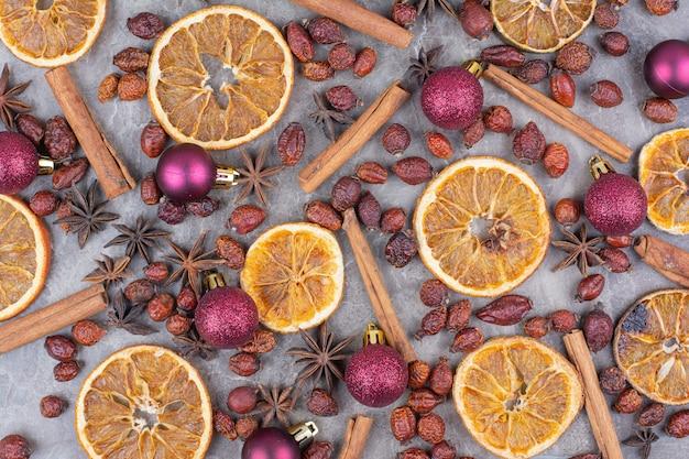 Orange Séchée Avec Des Boules De Noël Et Des Cynorrhodons Sur La Surface De La Pierre. Photo gratuit