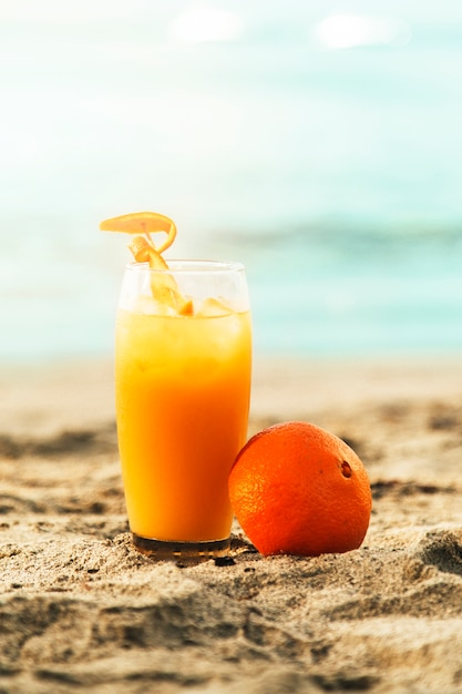 Orange et verre à jus posé sur une plage de sable fin Photo gratuit