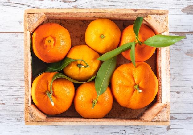 Oranges En Vue De Dessus De Boîte En Bois Sur Une Table En Bois Blanc Photo gratuit
