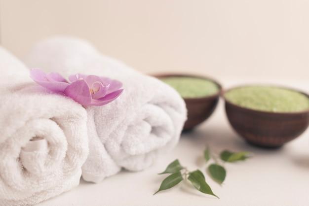 Orchidée sur une serviette roulée avec du sel de spa sur fond blanc Photo gratuit