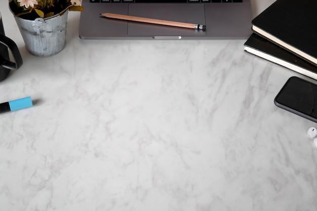 Ordinateur de bureau en marbre de bureau, livres, tasse à café et fleur. Photo Premium