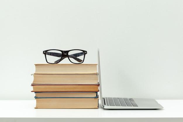 Ordinateur de bureau ouvert, livres et autres fournitures de bureau Photo Premium