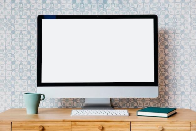 Ordinateur, clavier, tasse et journal intime sur le bureau en bois Photo gratuit