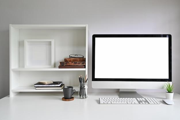 Ordinateur de maquette d'espace de travail sur le bureau et des livres, un cadre photo et des livres sur des étagères. Photo Premium