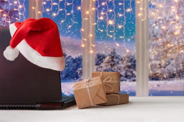 Ordinateur portable et cadeaux sur la table avec un chapeau de père noël à la maison avec une vue panoramique Photo Premium