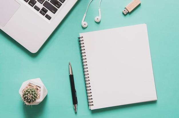 Ordinateur Portable Avec Cahier Vierge, Cactus, Stylo, Lecteur Flash, écouteur Sur Fond Bleu. Photo Premium