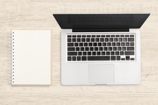 Ordinateur portable et cahier vierge sur une table en bois. Photo Premium