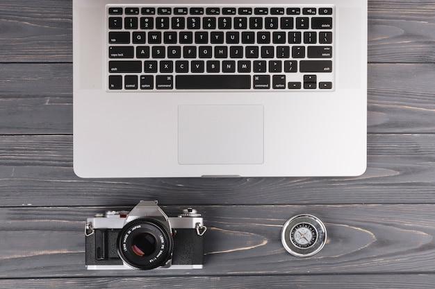 Ordinateur portable avec caméra et boussole sur une table en bois Photo gratuit