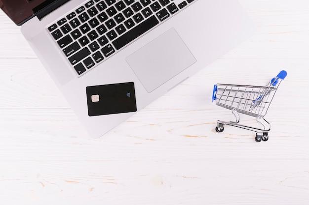 Ordinateur portable carte de voyage avec panier d'achat miniature sur un bureau en bois Photo gratuit