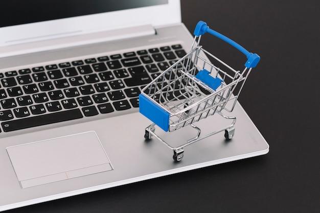 Ordinateur portable avec chariot de supermarché Photo gratuit