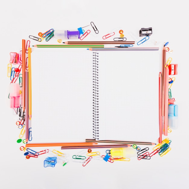 Ordinateur portable couché avec de la papeterie scolaire Photo gratuit