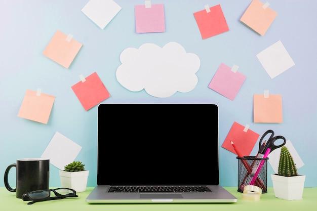 Ordinateur portable devant un mur avec du papier nuage et des notes adhésives Photo gratuit