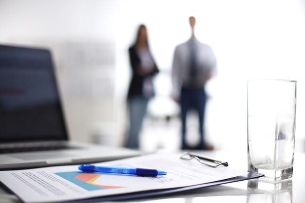 Ordinateur portable avec dossier sur le bureau, deux hommes d'affaires debout à l'arrière-plan Photo Premium