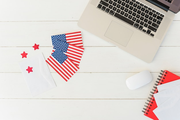 Ordinateur portable avec drapeaux américains sur une surface rayée Photo gratuit