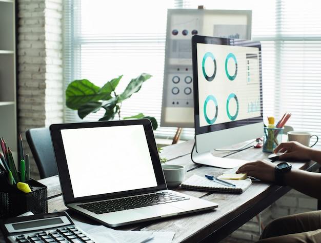 Ordinateur portable avec écran blanc sur une table dans un bureau hipster Photo Premium