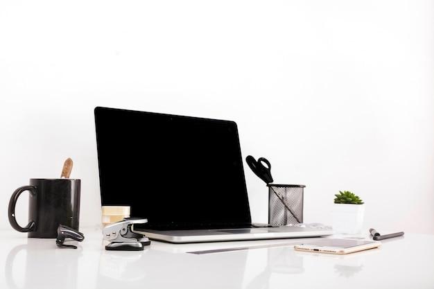 Ordinateur portable avec écran blanc et téléphone portable sur un bureau réfléchissant Photo gratuit
