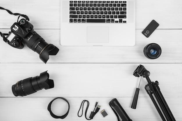 Ordinateur portable entouré d'accessoires pour appareils photo sur un bureau en bois blanc Photo gratuit
