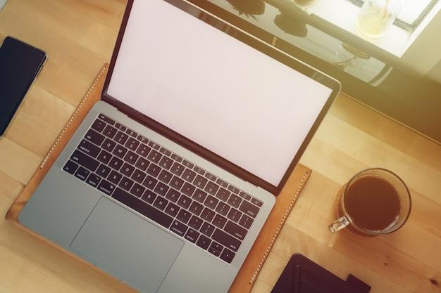 Ordinateur portable espace de travail indépendant sur un bureau en bois avec lumière de fenêtre. Photo Premium
