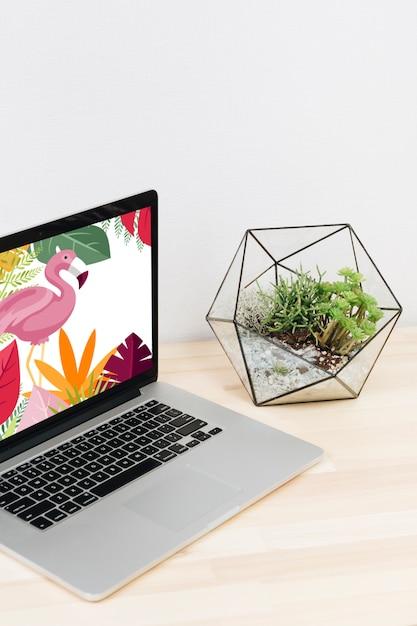 Ordinateur portable avec flamant rose à l'écran sur une table en bois Photo gratuit