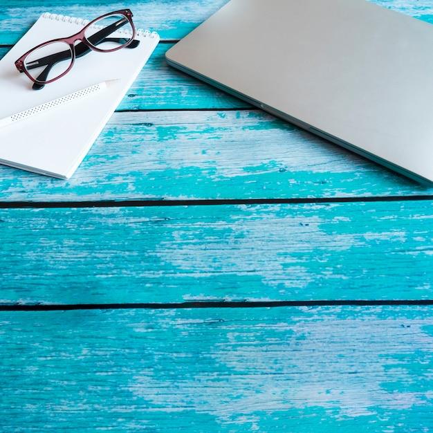 Ordinateur portable gris sur une table en bois bleue Photo gratuit