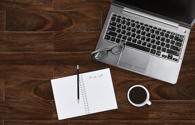 Ordinateur portable avec lunettes et cahier avec pour faire la liste sur un bureau en bois avec espace de copie. Photo Premium