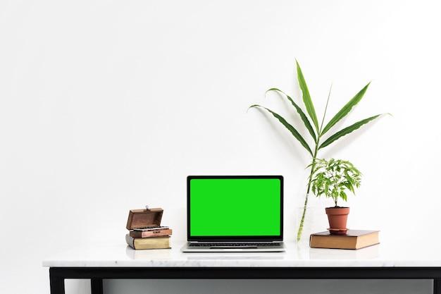 Ordinateur portable maquette avec écran vert sur le bureau de marbre avec feuille de nature mis sur la table Photo Premium