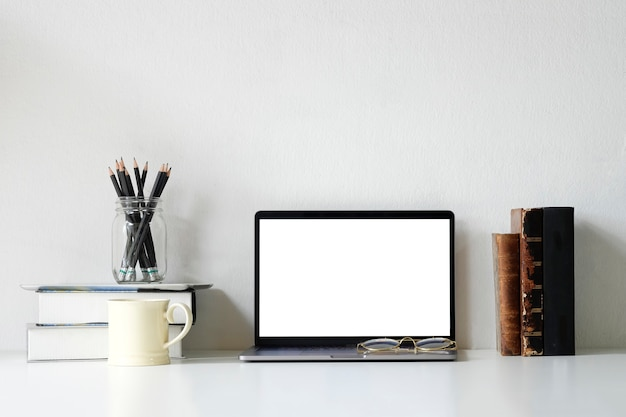 Ordinateur portable maquette de livres, crayon, crayon et tasse à café sur le bureau. Photo Premium