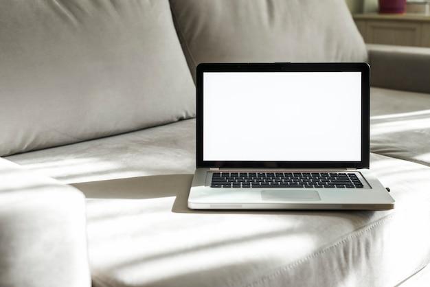 Un ordinateur portable ouvert avec écran blanc sur un canapé gris Photo gratuit