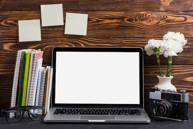 Un ordinateur portable ouvert avec un écran blanc vierge; appareil photo vintage; lunettes et livres sur le bureau en bois Photo gratuit
