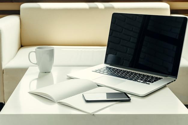 Ordinateur portable ouvert sur la table près du canapé, intérieur de la maison. concept de travail freelance Photo Premium