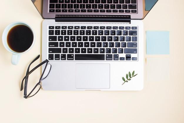 Un ordinateur portable ouvert; tasse de thé; lunettes et bloc-notes sur fond beige Photo gratuit