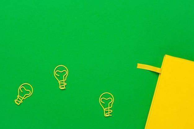Ordinateur portable avec des pages vierges et idée d'ampoule de trombone sur vert Photo Premium