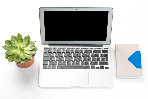 Ordinateur portable avec plante dans un pot et un cahier Photo Premium