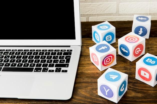 Ordinateur portable près de boîtes d'icônes d'application sociale sur table Photo gratuit