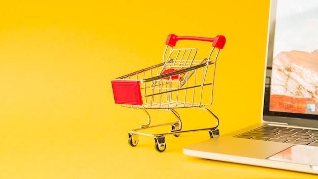 Ordinateur portable près de chariot de supermarché avec poignée rouge Photo gratuit