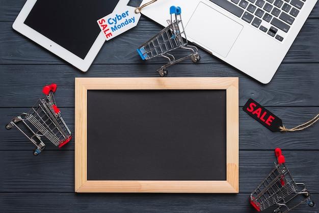 Ordinateur portable près de tag, tablette, chariot de supermarché et cadre photo Photo gratuit